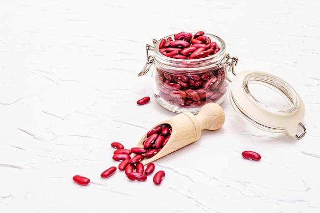 Séchez les haricots rouges ou les haricots rouges dans un bocal en verre. une précieuse source de protéines pour une alimentation végétalienne saine.