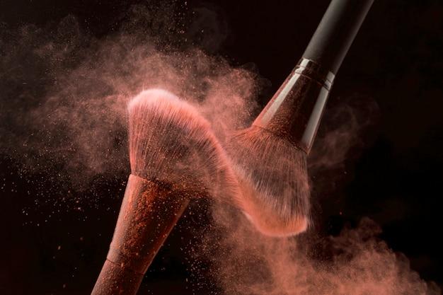 Secouant les brosses dans le nuage de poudre