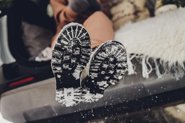 Secouer la neige des bottes, gros plan. avant de monter dans la voiture.