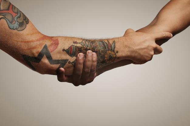 Secousse de l'avant-bras de deux jeunes amis masculins isolés sur blanc