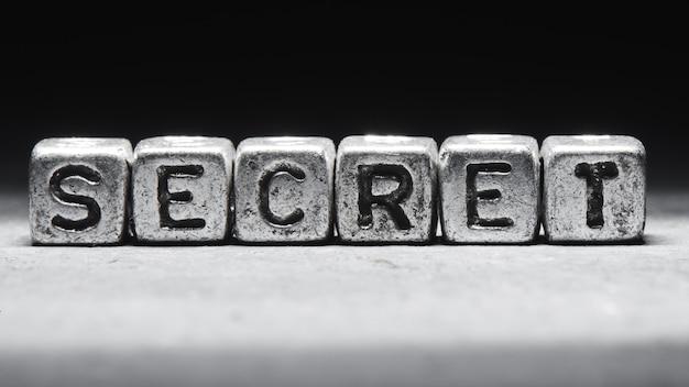 Secret d'inscription sur des cubes métalliques dans un style grunge sur fond noir isolé