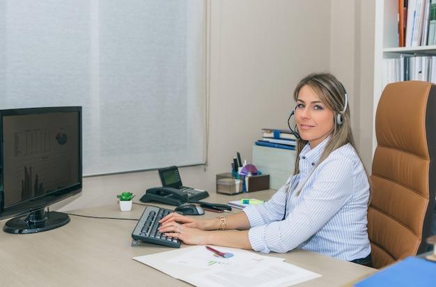 Secrétaire blonde souriante avec casque regardant la caméra tout en travaillant avec un ordinateur au bureau