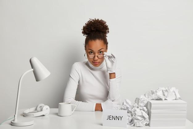 Secrétaire féminine sérieuse regarde attentivement à travers des lunettes, porte des gants blancs