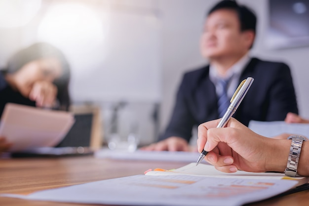 Secrétaire femme prenant des notes pour son patron lors d'une réunion d'affaires.