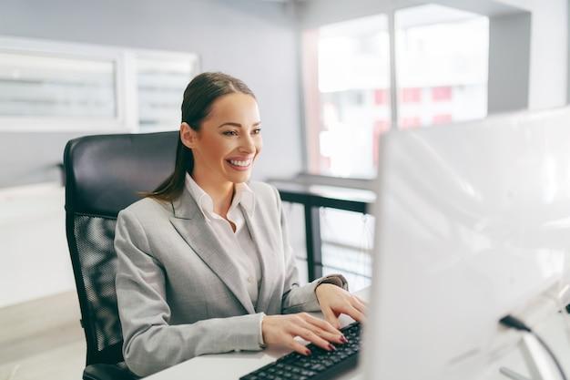 Secrétaire souriante vêtue de vêtements de cérémonie en tapant sur le clavier e-mail alors qu'il était assis au bureau.