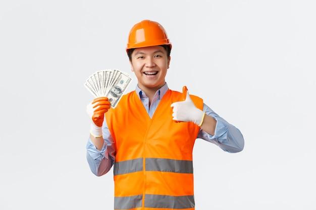 Secteur du bâtiment et concept de travailleurs industriels. heureux constructeur asiatique satisfait, directeur de la construction