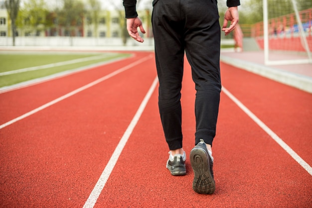 Section basse d'un athlète marchant sur une piste de course rouge