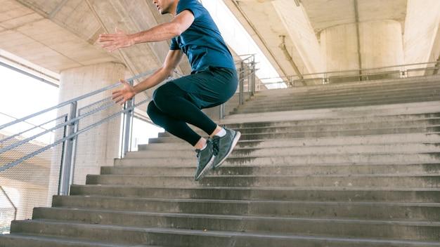 Section basse d'athlète masculin sautant dans l'escalier