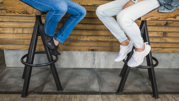 Section basse de deux amis masculins assis sur un tabouret de bar au restaurant