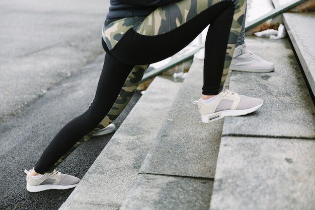 Section basse de deux joggeurs féminins s'étendant sur un escalier