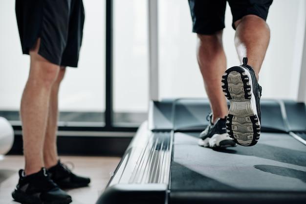 Section basse de l'entraîneur de fitness debout à côté du tapis roulant et contrôlant le clinet mature qui court pour s'échauffer avant l'entraînement