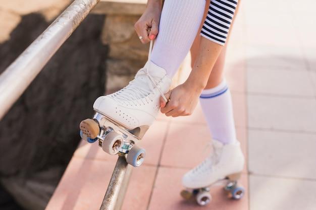 Section basse de la femme attachant la dentelle de patins à roulettes