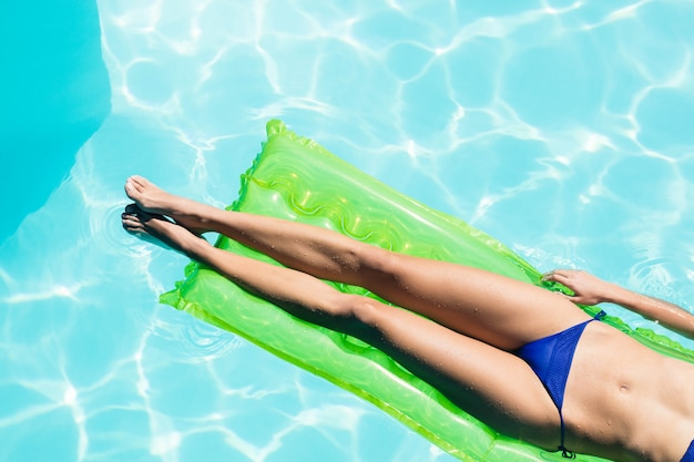Section basse de la femme sur lilo dans la piscine