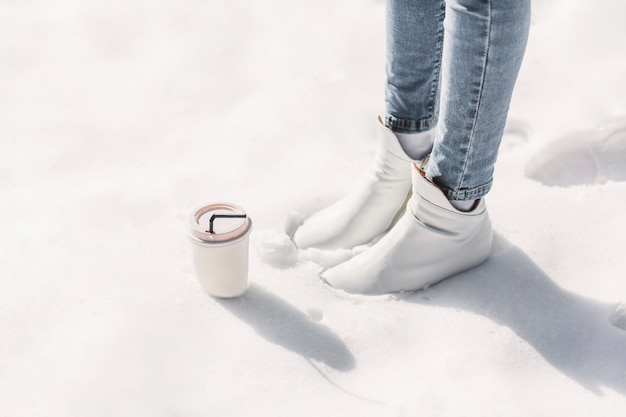 Section basse de la femme avec une tasse de café à emporter debout sur la neige