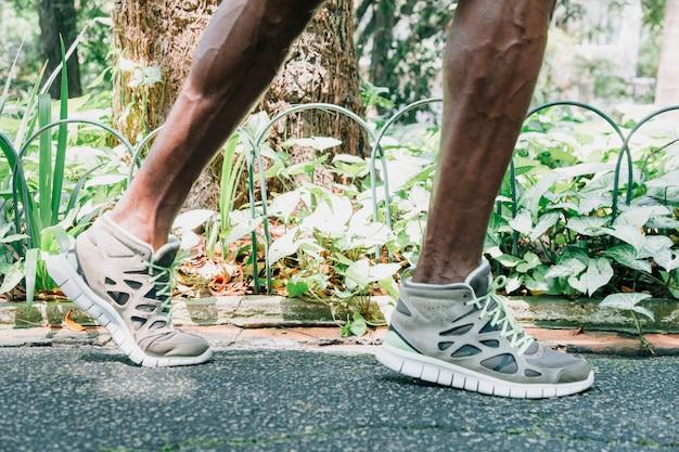 Section basse d'un jeune athlète masculin pieds dans le jardin