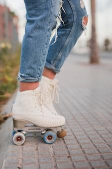 Section basse d'une patineuse en patins à roulettes blanches se tenant sur le trottoir