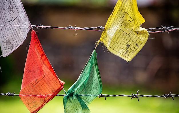 Une section de drapeau mantra avec fil de fer barbelé et flou