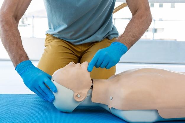 Section médiane d'un ambulancier paramédical pratiquant la réanimation sur mannequin