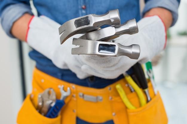 Section médiane de bricoleurs tenant des marteaux avec une ceinture d'outil autour de la taille