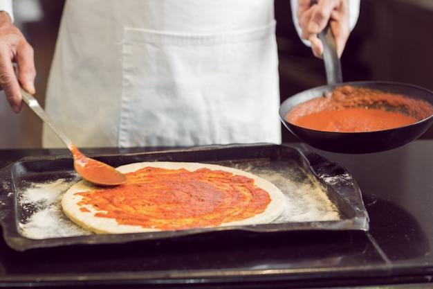 Section médiane d'un chef masculin préparant la pizza