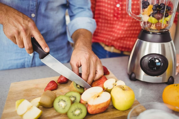Section médiane d'un couple préparant du jus de fruits