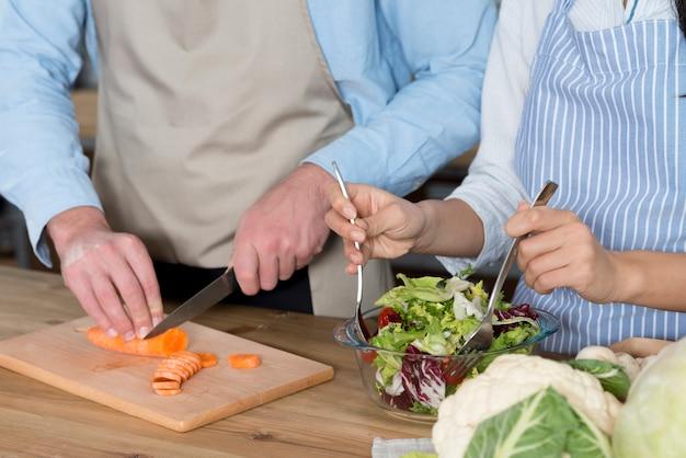 Section médiane d'un couple préparant un repas dans le comptoir de la cuisine