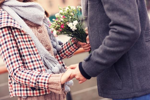Une section médiane d'un couple se tenant la main et des fleurs