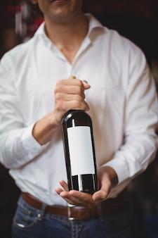 Section médiane du bar tendre tenant une bouteille de vin