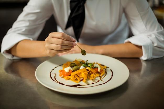 Section médiane du chef garnissant un plat de pâtes aux olives