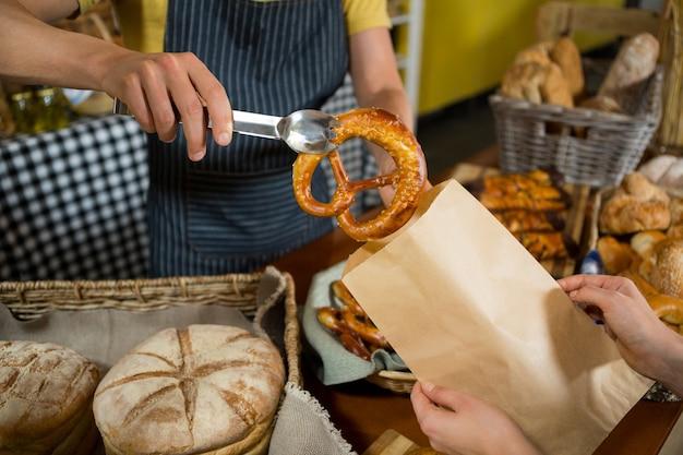 Section médiane du personnel d'emballage du pain bretzel dans un sac en papier au comptoir
