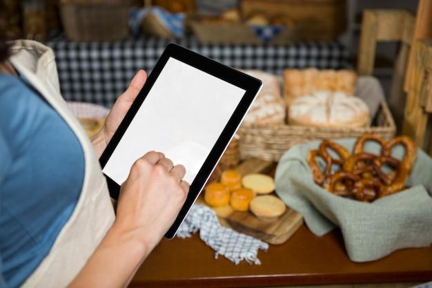 Section médiane du personnel utilisant une tablette numérique au comptoir de la boulangerie