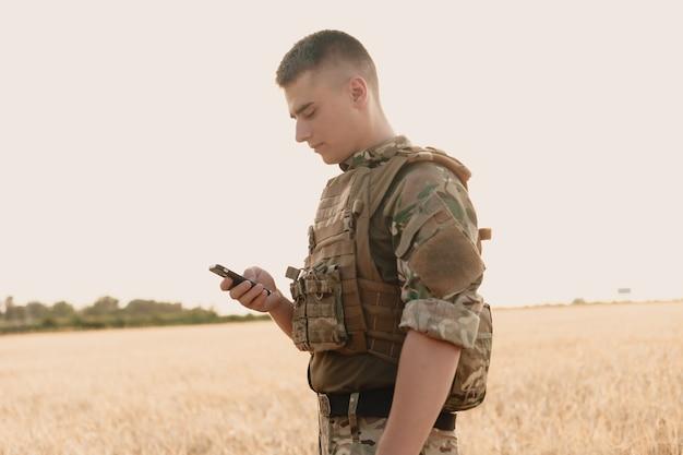 Section médiane du soldat militaire utilisant un téléphone portable dans le camp d'entraînement. lettre de guerre.