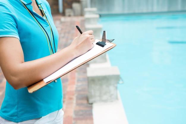 Section médiane de l'écriture d'entraîneur féminin sur le presse-papiers près de la piscine