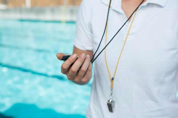 Section médiane de l'entraîneur féminin tenant un chronomètre au bord de la piscine