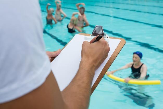 Section médiane de l'entraîneur de natation écrit sur le presse-papiers près de la piscine
