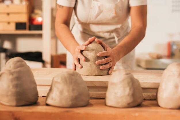 Section médiane d'une femme artisanale donnant forme à l'argile sur une table en bois