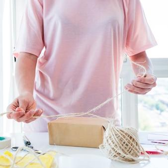 Section médiane d'une femme attachant les trois sur une boîte cadeau enveloppée au-dessus de la table