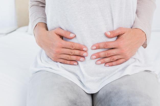 Section médiane d'une femme souffrant de douleurs à l'estomac dans une chambre d'hôtel