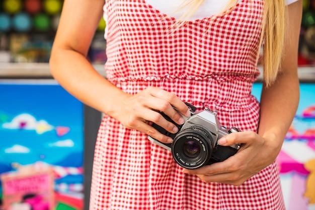 Section médiane de la femme tenant l'appareil photo à la main