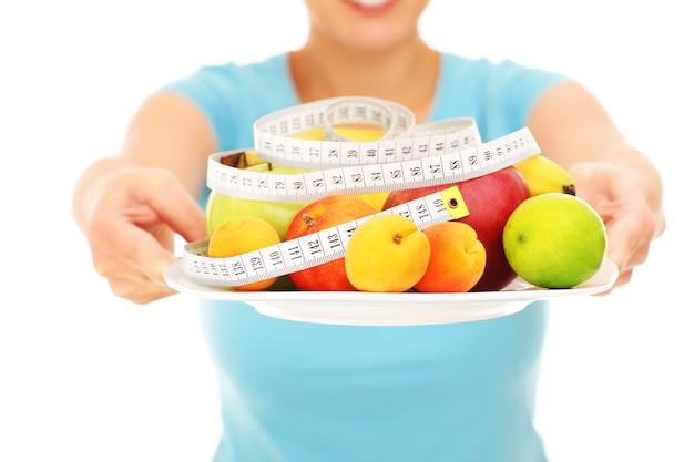 Une section médiane d'une femme tenant des fruits sur fond blanc