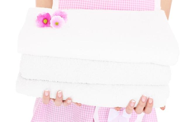 Une section médiane d'une femme tenant un tas de serviettes propres et de fleurs