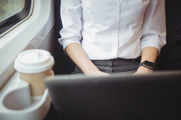 Section médiane de femme utilisant un ordinateur portable