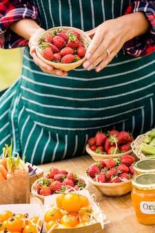 Section médiane d'une femme vendant des fraises