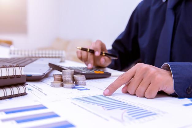 Section médiane de l'homme d'affaires calculant les taxes à l'aide de la calculatrice au bureau.