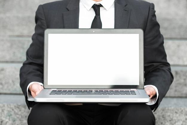 Section médiane d'un homme d'affaires montrant un ordinateur portable ouvert avec un écran blanc