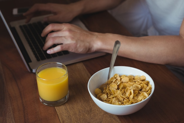 Section médiane de l'homme à l'aide d'un ordinateur portable tout en prenant le petit déjeuner dans la chambre