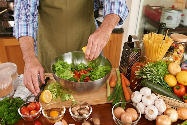 Section médiane d'un homme méconnaissable en tablier ajoutant du jus de citron à la salade fraîche