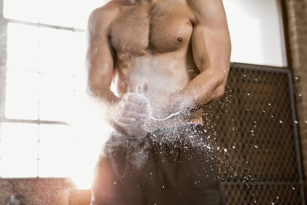 Section médiane d'un homme musclé appliquant de la poudre de craie