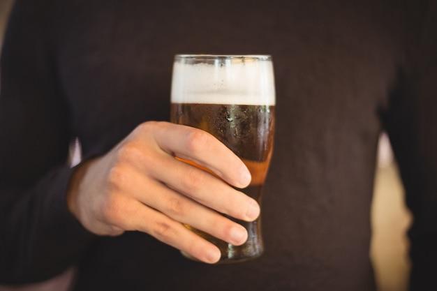 Section médiane de l'homme tenant un verre de bière