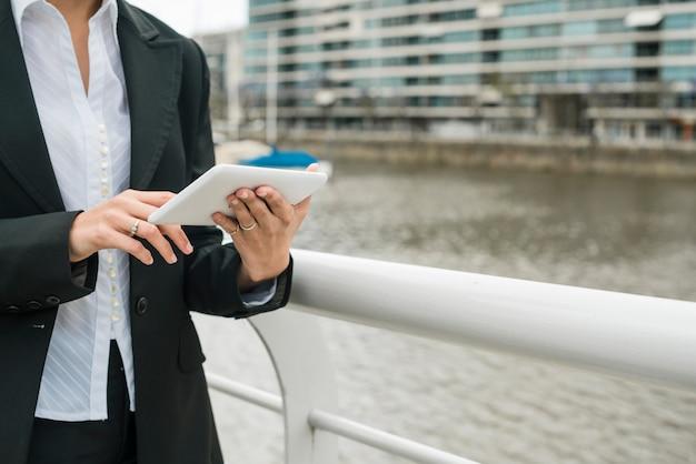 Section médiane d'une jeune femme debout près du port à l'aide d'un téléphone portable